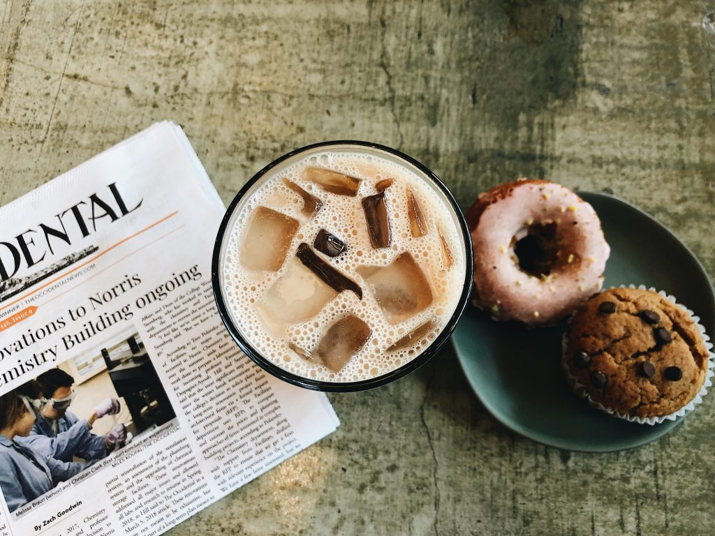 iced coffee newspaper and baked goods